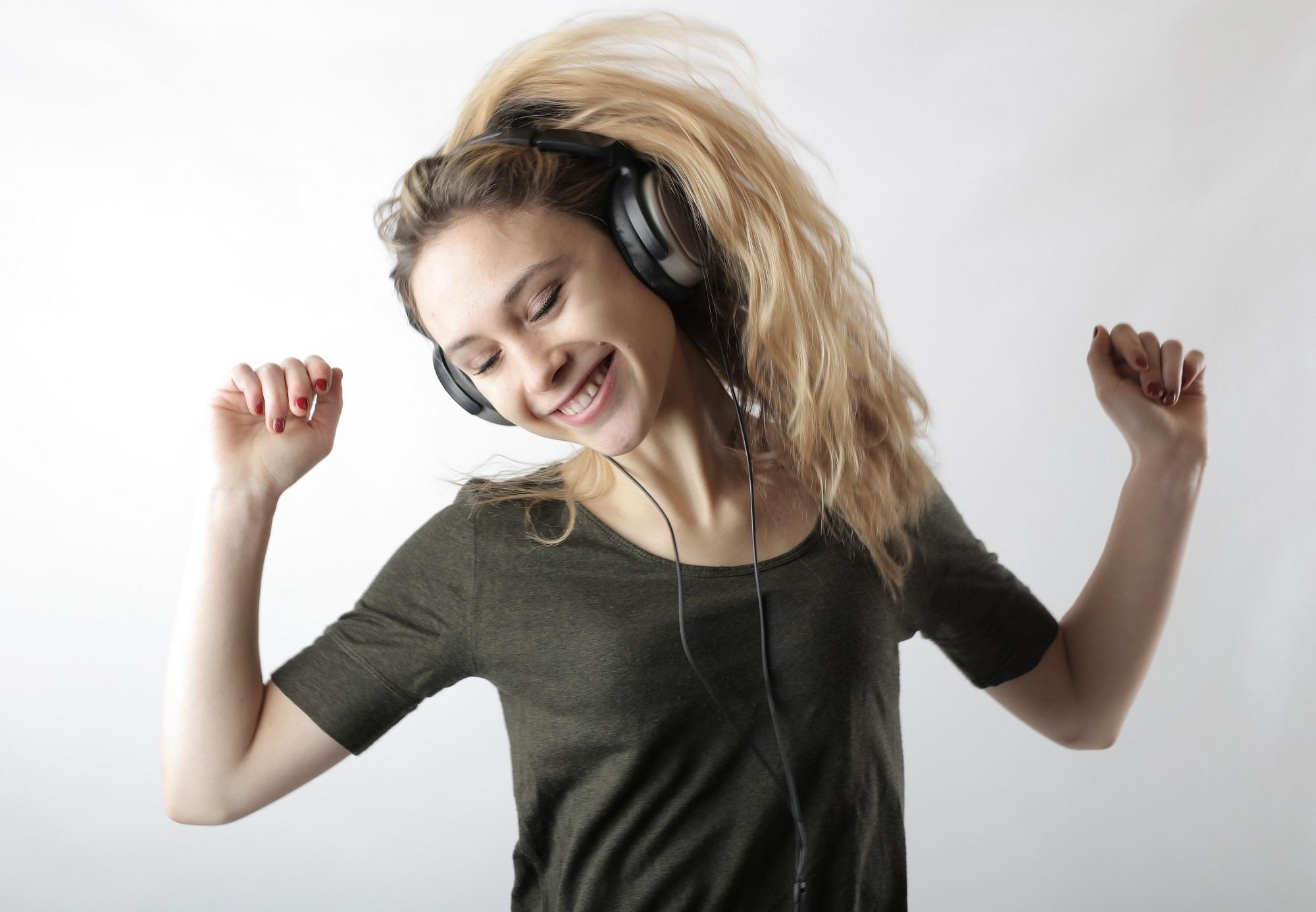 Fille Blonde Sourit En Ecoutant de la Musique